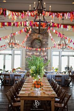 Decorate with colorful garlands for a pop of color at an indoor wedding
