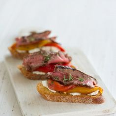Thinly sliced grilled NY steak on grilled slices of baguette with goat cheese, roasted peppers and fresh thyme.