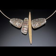 """Pam Caidin, """"The synergy that comes from the juxtaposition of contrasting shape, color and texture intrigues me. The forms are quiet to allow pattern and color to have weight. My intent is to create sculptural jewelry that is elegant and unpretentious.     With the use of a rolling mill, textured fine silver is inlayed with successive layers of rose, yellow & green 14K gold, nickel silver, then handformed into hollow pillows. Patterned pillows are combined with pillows of a single color…"""