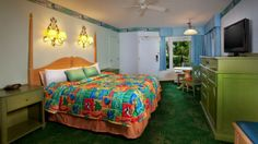 King bed with bright tropical-colored bedding opposite a green media cabinet with flat-screen TV Carribean Disney Hotels, Disney World Resorts, Walt Disney World, Caribbean Beach Resort, Beach Resorts, Organising Ideas, Media Cabinet, Disney Planning, Paint Colors