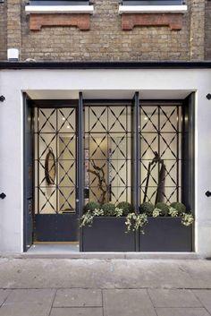 Hier ist ein Blick in den Eingangsbereich, erscheinen auf der Straße wie der Eingang zu einem stilvollen Geschäft oder Unternehmen. Der dekorative Metall-Bildschirm bietet Privatsphäre und sogar Platz für einen kleinen Garten.