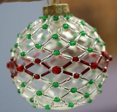 Netted Ornament Tutorial Don't you just love the beauty of a fully decorated tree? There's something so magical about coming home each day and seeing your tree covered in ornaments and lights. While every tree is gorgeous, the most beautiful…Read more › Beaded Ornament Covers, Beaded Ornaments, Christmas Baubles, Diy Christmas Ornaments, Homemade Christmas, Homemade Ornaments, Beaded Crafts, Christmas Tree, Beaded Christmas Decorations