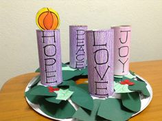 Pre-school kids can have fun with this DIY Advent Wreath. Toilet paper rolls or old soda cans wrapped in colored paper can resemble the candles, while cutout leaves and holly berries gathered on a plate resemble the evergreen wreath.
