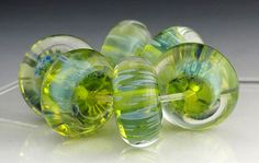 This set of 6 lampwork glass beads is bright spring green with a light blue speckled pattern beneath a deep layer of clear. The blue color reflects a mother-of-pearl luster. The beads are rondelle or disc shaped.