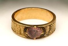 Late Medieval; mid 15th century. Gold ring, set with a purple spinel in a claw setting. There is an inscription around the sides.