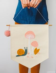 Follow our easy tutorial to make an adorable DIY felt banner with whimsical mushroom and snail designs. Hand stitch the project in only a couple hours!