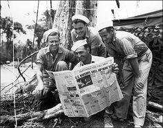 Sailors eagerly read an American newspaper during World War II .