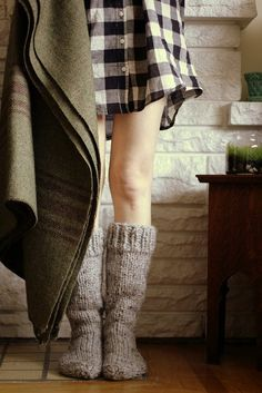 mix of textures and colors: warm wood, brick wall, buffalo check, wool socks and soft blanket
