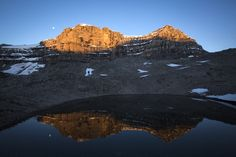 Alpine Start - My wife Meghan J. Ward (somewhat half-awake) makes her way past a little tarn at sunrise a few days ago, as the first light of day ignites two peaks of Cirrus Mountain. This is the other side of the twin peaks that rise above the Big Bend and the Weeping Wall when you drive along the Icefields Parkway. The mountain is rarely climbed and requires an incredibly beautiful approach. Shots from the summit ridge and that amazing approach coming in the next few days!