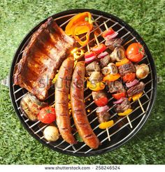 Tasty assortment of meat on a summer barbecue with sausages, beef kebabs and spare ribs with tomatoes and mushrooms, overhead view over green grass - Shutterstock Premier