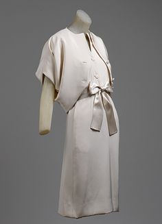 sleeveless afternoon dress made of white crepe, v neckline & revers. centre front closure, hip length jacket also in white crepe, rises to an inverted V at the ctr front waist, above-elbow sleeves are cut in one with the body. met museum