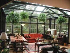 verrière extérieure noire, aménagée avec de meubles en bois, un joli sofa contrastant, végétation qui surplombe le décor vintage