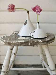 old enamal funnels made into bud vase holder sitting on top of an old chair without back