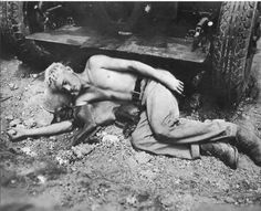A war weary Marine and his devil dog sleeping on the rocky ground of Okinawa