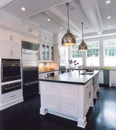 source: Weitzman Halpern Design Chic modern kitchen with ebony stained wood floors, glossy white box beams, white kitchen cabinets & kitchen island with black quartz countertops and industrial pendants.