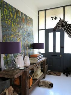 Huge painting, old rustic workbench, glass lamps with purple shades, white pitchers, giant cast foot, zebra head and cute pug. 47 Park Avenue's home