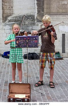 Young violist buskers playing the violin on street for money - Stock Image
