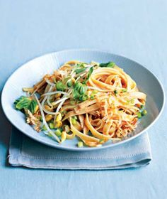 8 ounces rice noodles or fettuccine  1 13.5-ounce can unsweetened coconut milk  3 tablespoons tomato paste  1 teaspoon chili powder  1 teaspoon kosher salt  1 tablespoon chili paste or sauce (optional)  3 scallions, thinly sliced  8 ounces bean sprouts  16 basil leaves, whole or torn  1/4 cup shredded coconut, toasted (optional)