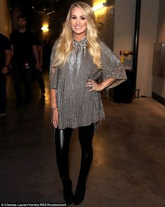 8ebd89b5068a5 Carrie Underwood conceals her baby bump beneath a blouse as she attends the  iHeart Radio Festival