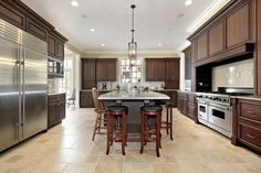 Large custom kitchen with dark brown cabinets, stainless steel appliances (with extra large refrigerator) and large island.