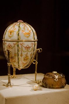 Imperial Gatchina Palace Egg – Fabergé, 1901; workmaster, Mikhail Perkhin; crafted from gold, opalescent white enamel, silver-gilt, portrait diamonds, rock crystal, and seed pearls; 4 15/16 x 3 9/16 in. (12.5 x 9.1 cm); the egg opens to reveal the surprise a scaled model gold replica of the palace at Gatchina, the Dowager Empress's principal winter residence outside Saint Petersburg. It is one of two imperial Easter eggs held in the Walters Art Museum in Baltimore, Maryland.