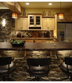Acid stained concrete counter top with stone bar. Love the undercounted lighting too.