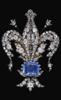 SAPPHIRE AND DIAMOND BROOCH, LATE 19TH CENTURY Designed as a fleur de lys decorated with cushion-shaped, circular-, single-cut and rose diamonds, set at the centre with a cushion-shaped sapphire, detachable brooch fitting later added.