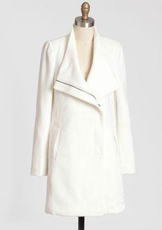This sleek cream-hued wool-blend coat is completed with vertical welt pockets and an asymmetrical zipper closure. Finished with padded shoulders, this elegant coat is a definite cold-weather staple