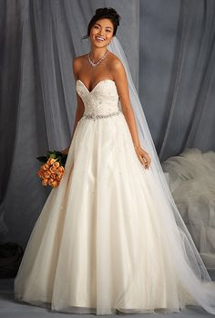 The Alfred Angelo Collection. Awe-inspiring natural waist ball gown in net over satin. Fitted bodice features a strapless sweetheart neckline fully embellished with crystal beading, rhinestones and silver beads.  The waist is accented with a dramatic rhinestone trim. Full gathered net overlay skirt has scattered beading to match and a chapel length train. Also available with straps as style 2572.moreless