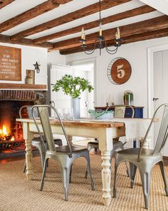 To help the dining room feel more spacious, homeowner Jaime Costiglio painted the walls white and tore down a plaster ceiling to reveal original timbers that show off the house's post-and-beam construction. The table is a refinished castoff from a friend.  #remodel #homeimprovement #homeimprovementideas #diningroom #diningroomideas #diy #homedecor