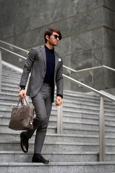 Men's Navy Sunglasses, Navy Polo, White Pocket Square, Charcoal Suit, Dark Brown Leather Tassel Loafers, and Grey Leather Briefcase