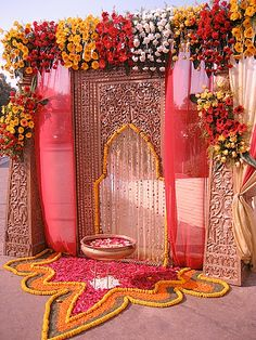 The main entrance to this Indian wedding's event hall is a gorgeous pattern that combines classic customs with a contemporary look. Perfect with a marigold garland and colorful curtains.