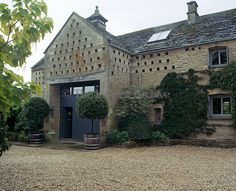 The front facade of Vanessa McDowell's converted barn in the Cotwolds features an original dovecote above the front entrance