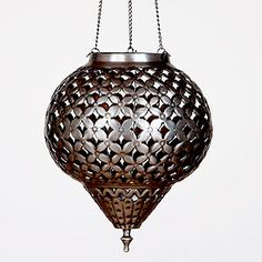 Timeworn techniques and traditional patterns were used to create our Medium Punched Metal Hanging Lantern. Skilled artisans in India expertly hand punched metal pieces with authentic shapes and patterns then formed them into this Hanging Lantern's traditional silhouette. The metal was then given an antiqued zinc finish. Soft light escapes through the cutouts when lit from within, casting beautiful constellations on the wall.