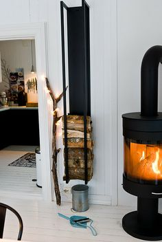 wood burner / fireplace and a really fabulous wood storage device hanging on the wall that is complete genius... Stacking the wood in a succinct pattern is quite beautiful as well as greatly functional...& brings nature into the house year around as decor!!!