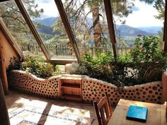 The interior of an earthship, with a built-in planter on the south side of the home.