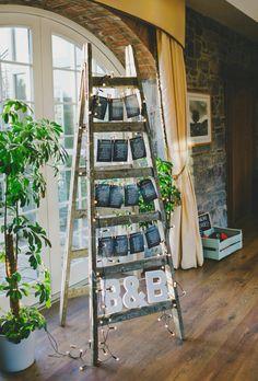 idée de plan de table pour mariage vintage, liste invités noires sur un escabeau, guirlande lumineuse, lettres blanches couple marié