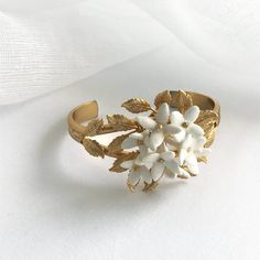 The White Annabelle Bracelet's sweet design is made up of a cluster of white handcrafted flowers framed by tiny golden leaves. Golden Leaves, Flower Frame, Cuffs, Stud Earrings, Bracelets, Flowers, Jewelry, Design, Bangle Bracelets