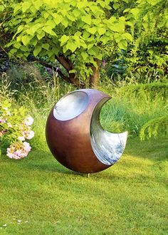 Bite copper sphere in a pretty garden