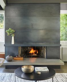 A Blackened Steel Fireplace Surround With A Concrete Hearth Is A Strong Look Inside This Mid-Century Modern House Metal Fireplace, Concrete Fireplace, Home Fireplace, Fireplace Hearth, Fireplace Remodel, Living Room With Fireplace, Fireplace Surrounds, Modern Fireplace Tiles, Modern Fireplace Mantles