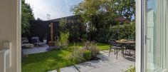 1 kleine-tuinontwerp-inspiratie-loungehoek-groenblijvende-bamboe-en-siergrassen-mbi-geoceramica-grind-zwart-rabat-schutting