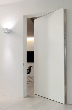 Concealed door between casual dining and boot room  L'Invisible white pivoting frameless door. << Secret door......... Nice onneee