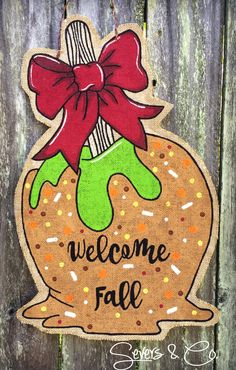 Brand new for Fall Caramel Apple burlap door hanger by Severs & Co… Halloween Door Hangers, Fall Door Hangers, Burlap Door Hangers, Wooden Hangers, Burlap Door Decorations, Burlap Projects, Burlap Crafts, Painted Doors, Painted Signs