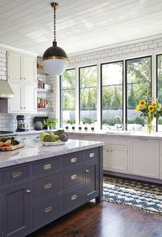 Love the gray kitchen island paired with white upper cabinets, carrara marble counters, industrial pendant light and black trimmed windows.