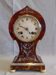 Antique tortoiseshell mantel clock with silver inlay and stringing and ivory feet. England, ca.1895.