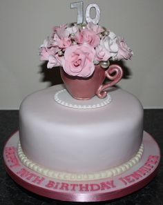 70th birthday cake featuring a gumpaste teacup filled with roses in various shades of pink and wired pearl beads.