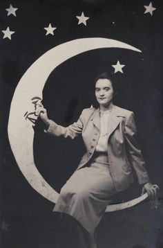 A woman posing on a smiling paper moon, 1940s.