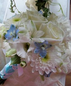 White roses, lisianthus and cushion poms with a few pops of blue delphinium buds.