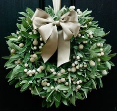 This simple yet elegant Christmas door wreath boasts a wonderfully scented bundle of fresh sage, teamed with white frosted and brunii berries.