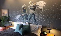 """O """"The Walled Off Hotel"""" abriu as portas na manhã desta sexta-feira para a imprensa. Localizado em Belém, na Cisjordânia, o local está repleto de obras do artista de rua Banksy e conta com 9 quartos, todos com a """"pior vista do mundo"""".   Localizado bem em frente ao famoso muro construído por Israel para impedir a entrada de """"&qu..."""